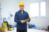 Glimlachende man in helm met handschoenen over kamer — Stockfoto