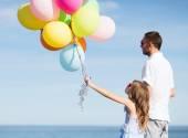 Vader en dochter met kleurrijke ballonnen — Stockfoto