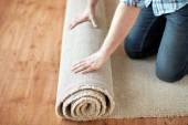 Close up of male hands rolling carpet — Stock Photo