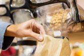 Close-up van de hand gieten noten te papieren zak — Stockfoto