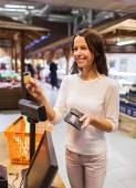 Happy woman with credit card buying food in market — Stock Photo