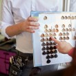 Woman choosing hair color from palette at salon — Stock Photo #73568065
