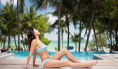 Happy woman in bikini tanning over summer beach — Stock Photo