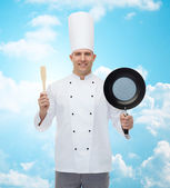 Happy male chef holding frying pan and spatula — Stockfoto