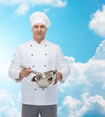 Happy male chef cook whipping something with whisk — Stock Photo