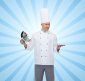 Happy male chef cook opening cloche — Stockfoto