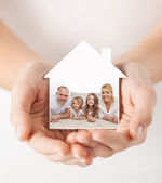 Close up of hands holding house shape with family — Stock Photo