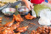 Close up of cook hand with tongs grilling chicken — Stock Photo