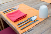 Close up of cutlery with glass and napkin on table — Stock Photo