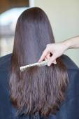 Hand with comb combing woman hair at salon — Stock Photo