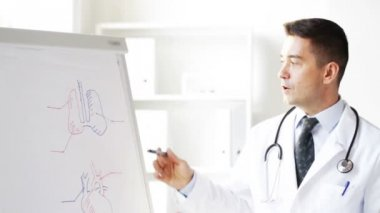 Happy doctor showing medical drawing on flip board — Stock Video