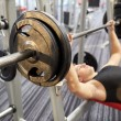 Close up of man flexing biceps with barbell in gym — Stock Photo #73764217