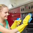 Happy woman cleaning cooker at home kitchen — Stock Photo #73764561