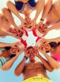 Lachende vrienden in cirkel op zomer strand — Stockfoto