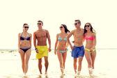 Lachende vrienden in zonnebril op zomer strand — Stockfoto