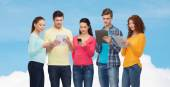 Group of teenagers with smartphones and tablet pc — Stockfoto