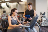 Woman with trainer on exercise bike in gym — Stockfoto