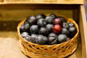 Ripe plums in basket at farm or food market — Stock Photo