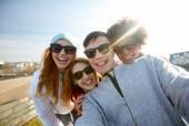 Group of happy friends taking selfie on street — Стоковое фото