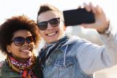 Happy teenage friends in shades taking selfie — Stock Photo