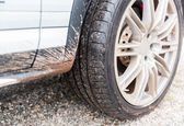 Close up of dirty car wheel on ground — Stock Photo