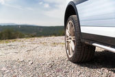 Close up of dirty car wheel on cliff — Stock Photo
