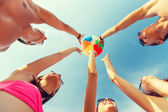 Smiling friends in circle on summer beach — Stock Photo