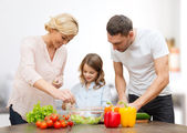 Happy family cooking vegetable salad for dinner — Fotografia Stock