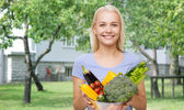 Smiling young woman with vegetables in home garden — Stock Photo