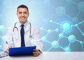 Happy doctor with clipboard over blue background — Stockfoto
