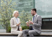 Smiling businessmen with paper cups outdoors — Stock Photo