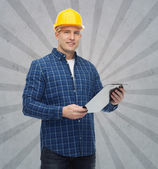 Smiling male builder in helmet with clipboard — Fotografia Stock