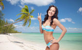 Happy woman in swimsuit showing victory hand sign — Fotografia Stock