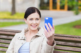 Smiling woman taking picture with smartphone — Stock Photo