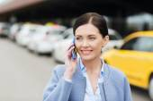 Smiling woman with smartphone over taxi in city — Fotografia Stock
