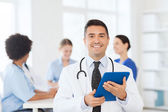 Happy doctor with tablet pc over team at clinic — Stock Photo