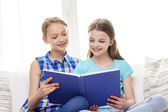 Two happy girls reading book at home — Stock Photo