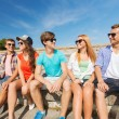 Group of smiling friends sitting on city street — Stock Photo #74319107