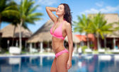 Happy young woman in pink bikini swimsuit on beach — Fotografia Stock