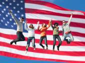 Smiling friends in sunglasses jumping high — Stock Photo