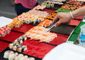 Close up of hand with tongs taking sushi — Stock Photo