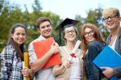 Group of smiling students with diploma and folders — Fotografia Stock
