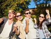 Group of happy friends showing triumph gesture — Stock fotografie