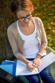 Happy student girl writing to notebook at campus — Fotografia Stock