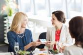 Happy women giving birthday present at restaurant — Stock Photo