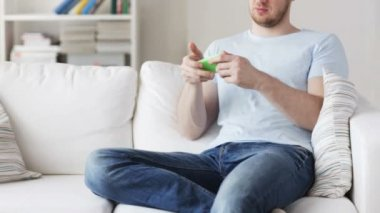 Close up of man playing game on smartphone at home — 图库视频影像