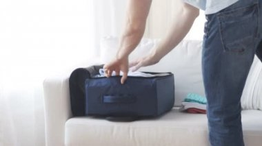 Close up of man packing clothes into travel bag — 图库视频影像