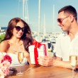 Smiling couple with gift box cafe — Stock Photo #74719495