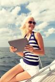 Smiling woman sitting on yacht with tablet pc — Stock Photo