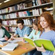 Happy students reading books in library — Stock Photo #74723985